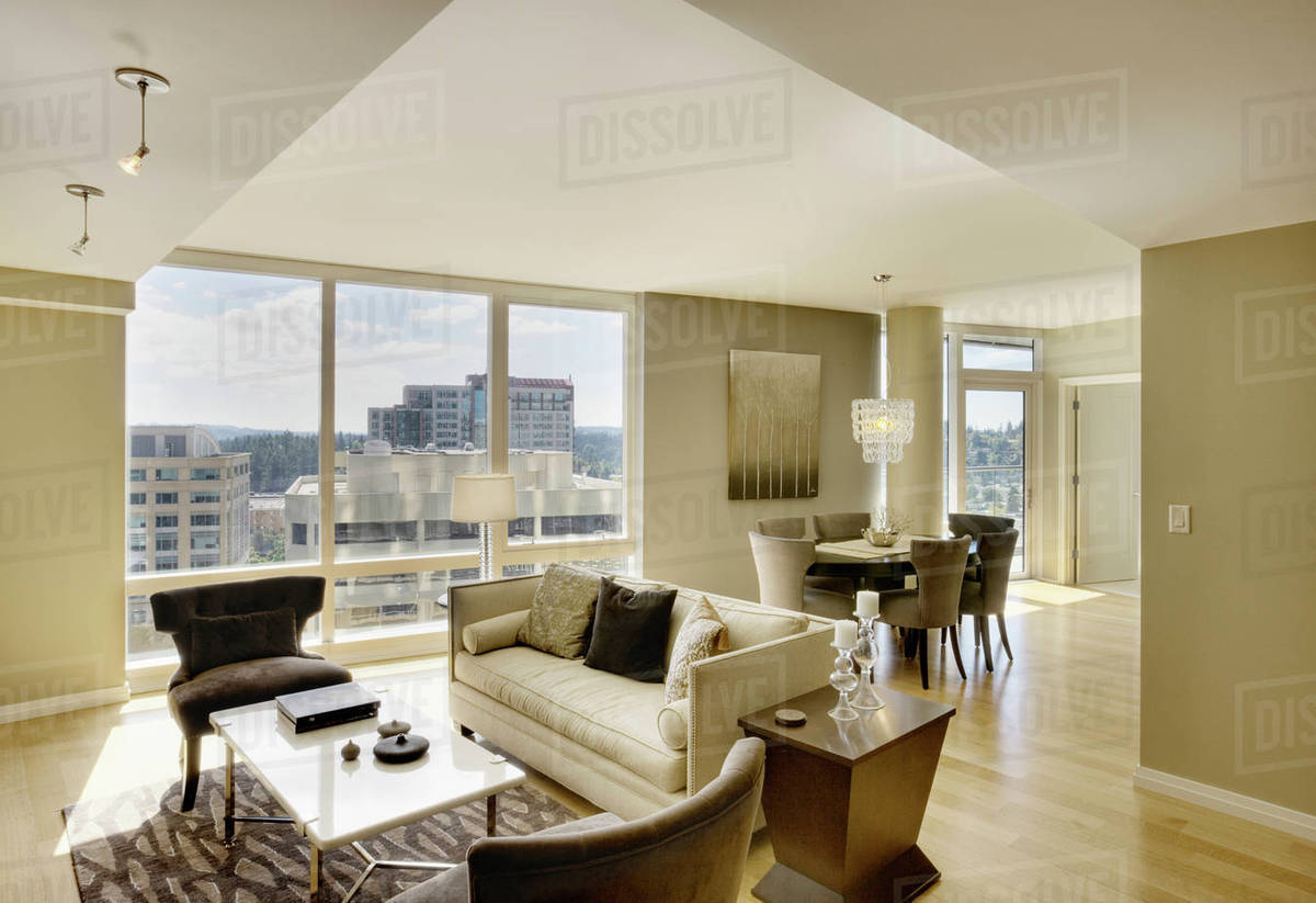 Sun shining through windows of open floor plan in luxury highrise apartment  stock photo