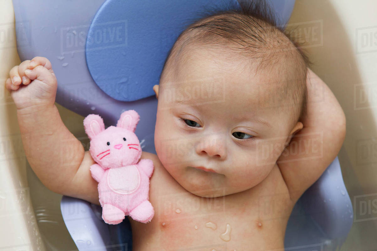 Mixed race Down Syndrome baby laying in plastic bathtub stock photo