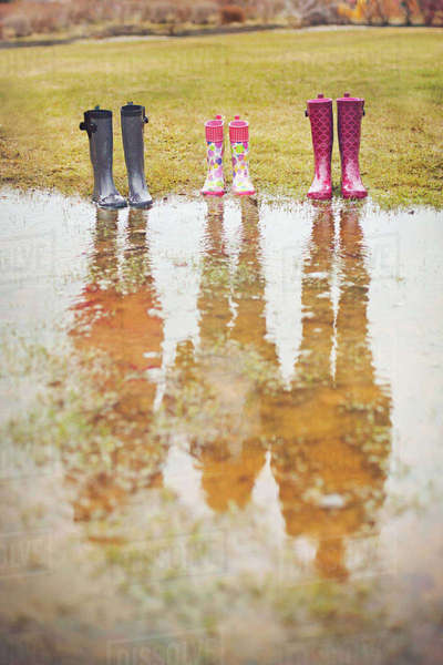Reflection of people from rain boots in puddle Royalty-free stock photo
