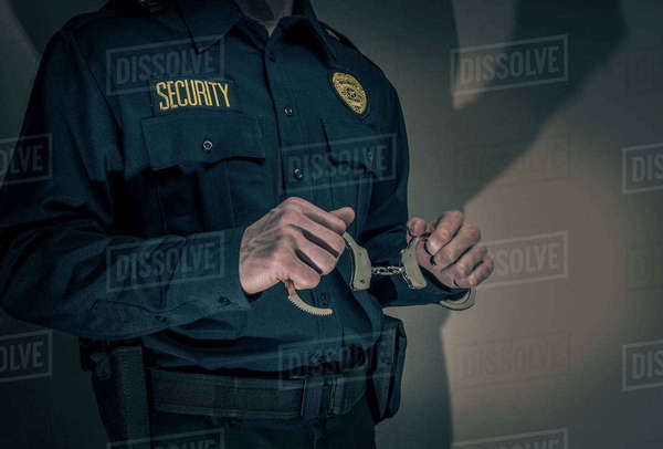 Caucasian security officer holding handcuffs  Royalty-free stock photo