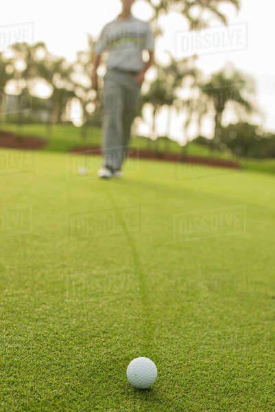 Caucasian man walking to golf ball on golf course green Royalty-free stock photo