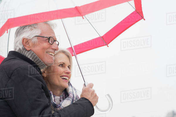 Older Caucasian couple standing under umbrella Royalty-free stock photo