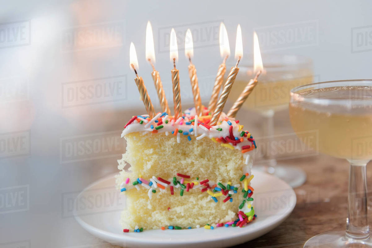 Candles Burning On Slice Of Cake With Sprinkles Near Champagne