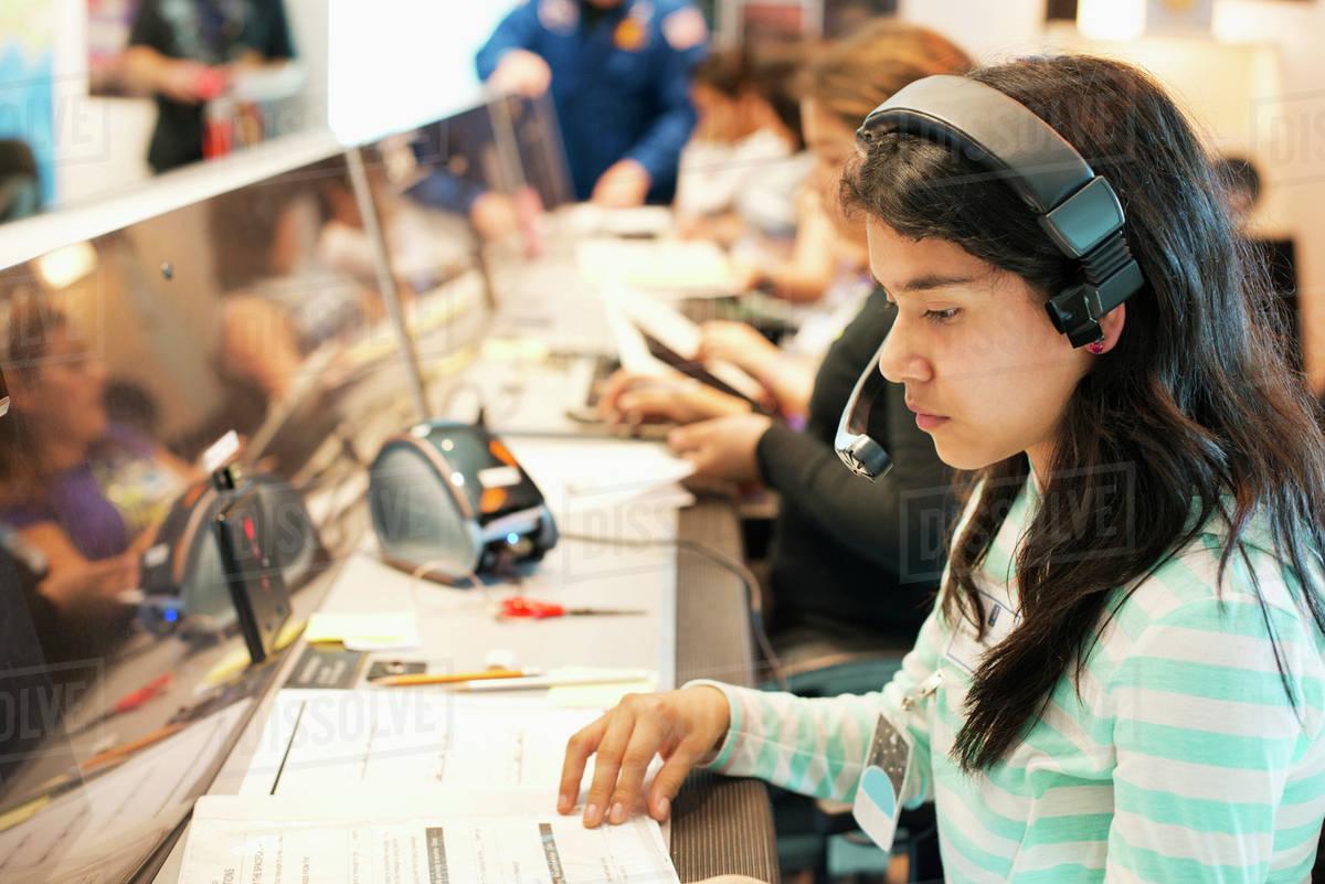 Hispanic student listening to headset at desk Royalty-free stock photo