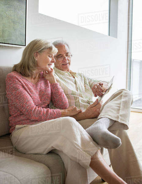 Older Caucasian couple using digital tablet on sofa Royalty-free stock photo