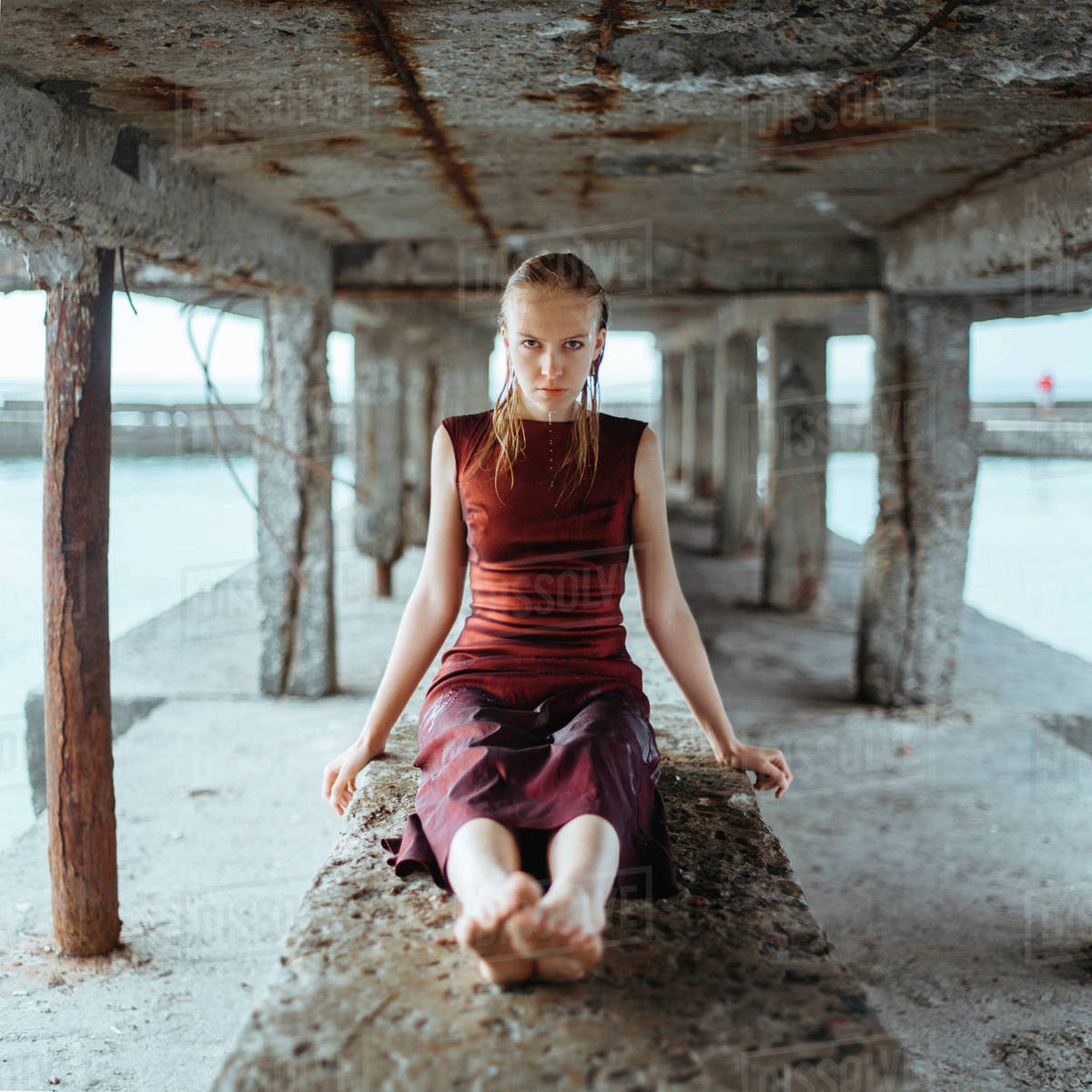 Caucasian girl wearing wet dress sitting underneath dock