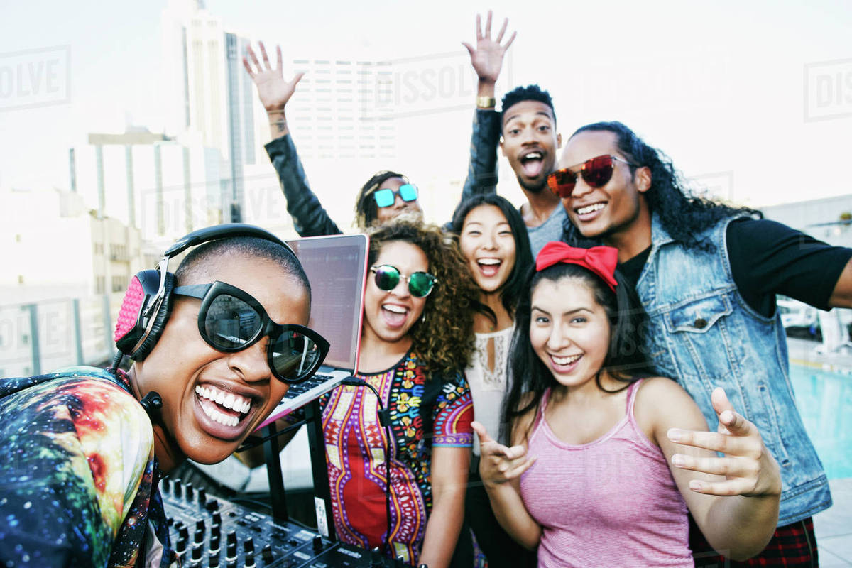 Friends smiling with DJ on urban rooftop Royalty-free stock photo
