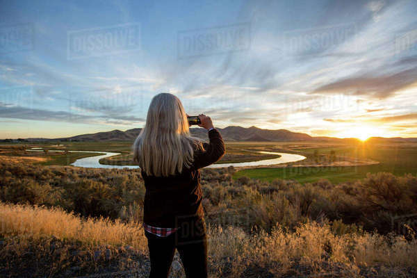 Caucasian woman photographing sunset over winding river Royalty-free stock photo