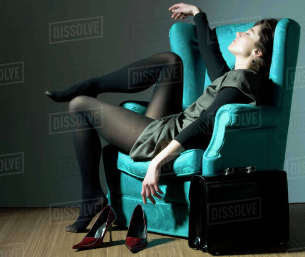 Fatigued Caucasian businesswoman unwinding in blue armchair Royalty-free stock photo
