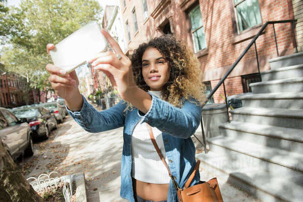 Mixed Race woman in city posing for cell phone selfie Royalty-free stock photo