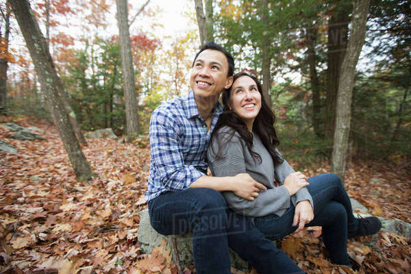 Couple sitting on rock in forest during autumn Royalty-free stock photo
