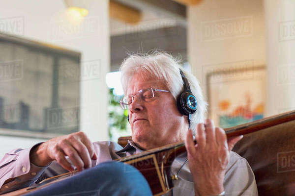 Man listening to headphones and playing guitar Royalty-free stock photo