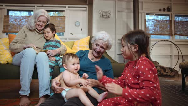 Grandmothers and grandchildren relaxing in livingroom Royalty-free stock video