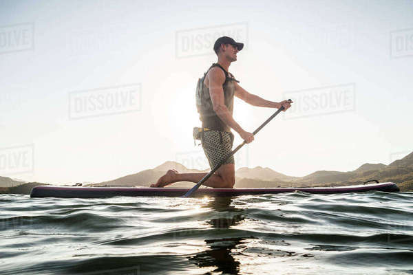 Man kneeling on paddleboard in river Royalty-free stock photo