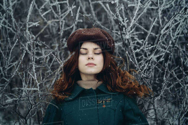 Woman with eyes closed near icy branches Royalty-free stock photo