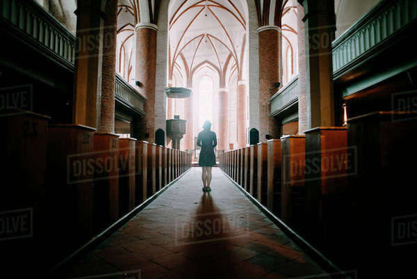 Caucasian woman standing in aisle of church Royalty-free stock photo