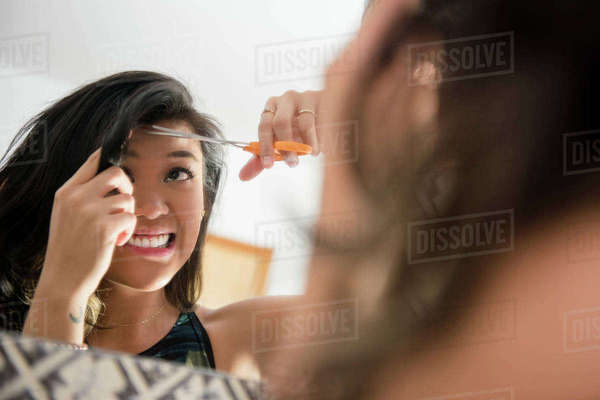 Uncertain Mixed Race woman cutting bangs with scissors Royalty-free stock photo