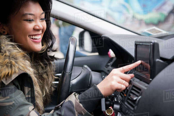 Mixed Race woman driving car pressing touch screen Royalty-free stock photo