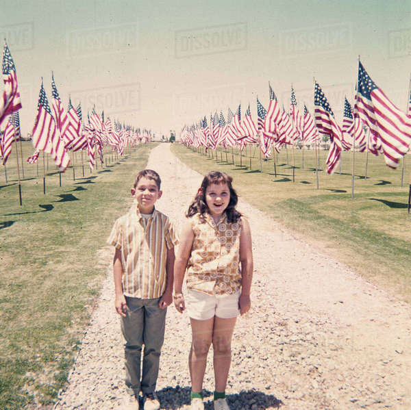 Caucasian brother and sister holding hands near American flags Royalty-free stock photo