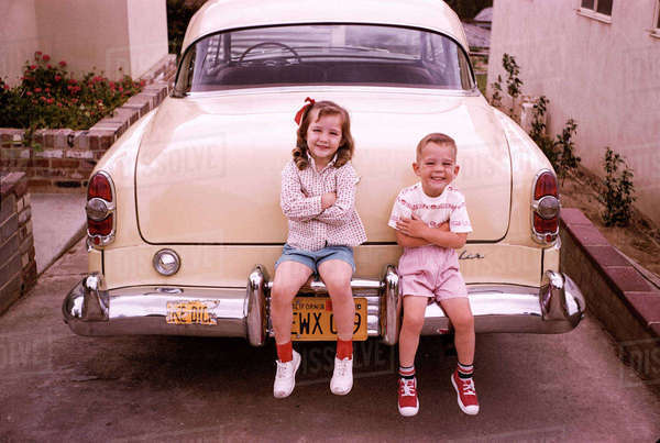 Caucasian brother and sister sitting on bumper of vintage car Royalty-free stock photo