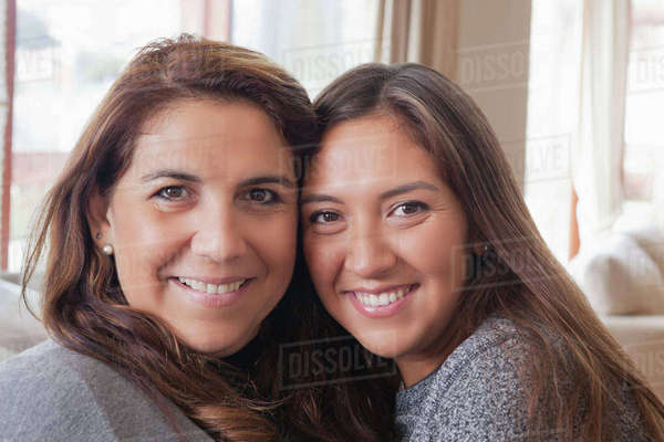 Smiling Hispanic mother and daughter posing cheek to cheek Royalty-free stock photo