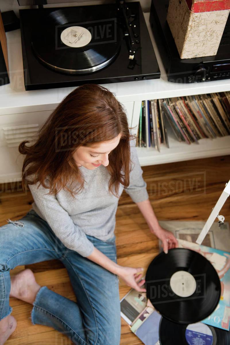 Caucasian Woman Sitting On Floor Examining Vinyl Record D145 274 358
