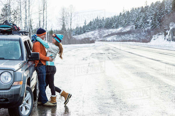 Caucasian couple hugging near car in winter Royalty-free stock photo