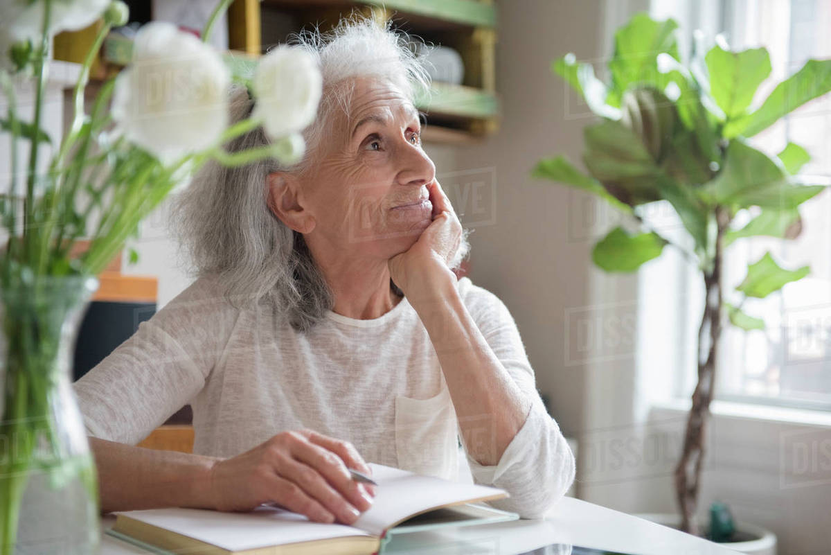 pensive older woman writing in journal - stock photo - dissolve