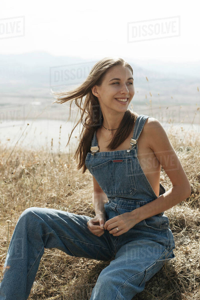 Caucasian Woman Wearing Overalls Sitting In Field Stock Photo Dissolve