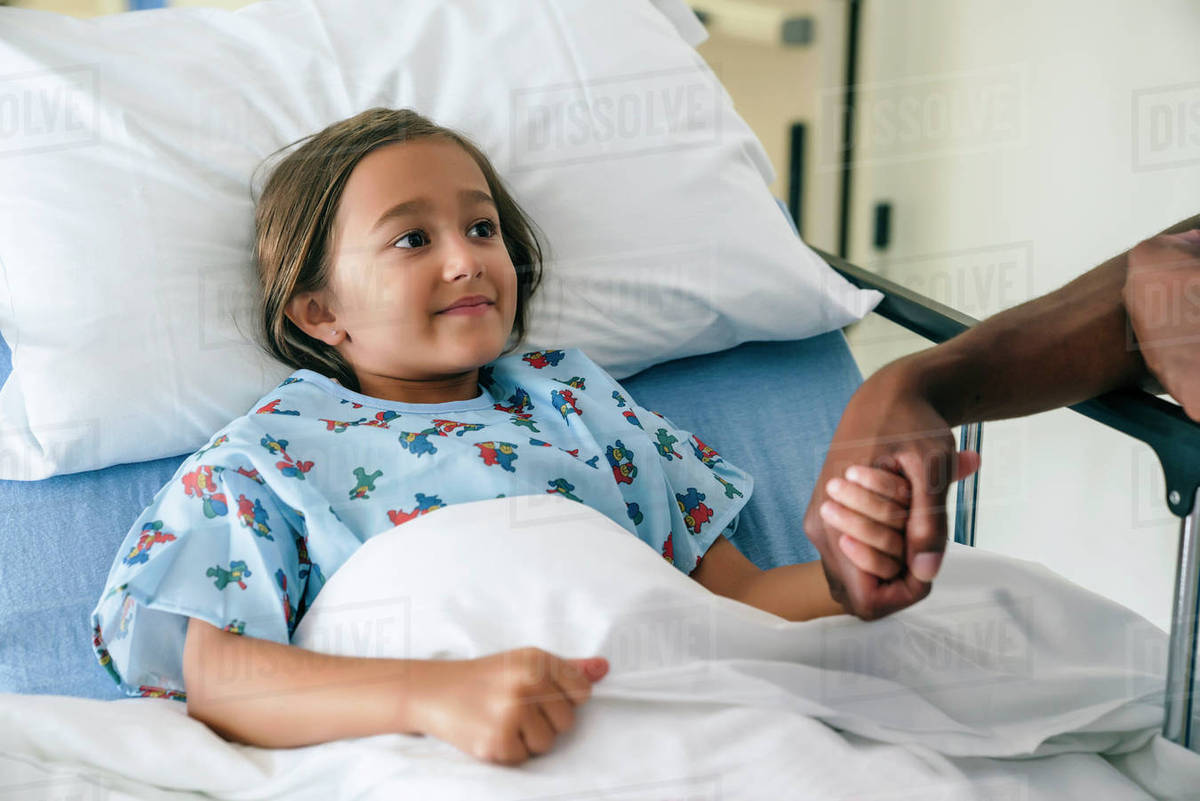 Man Holding Hands With Girl In Hospital Bed