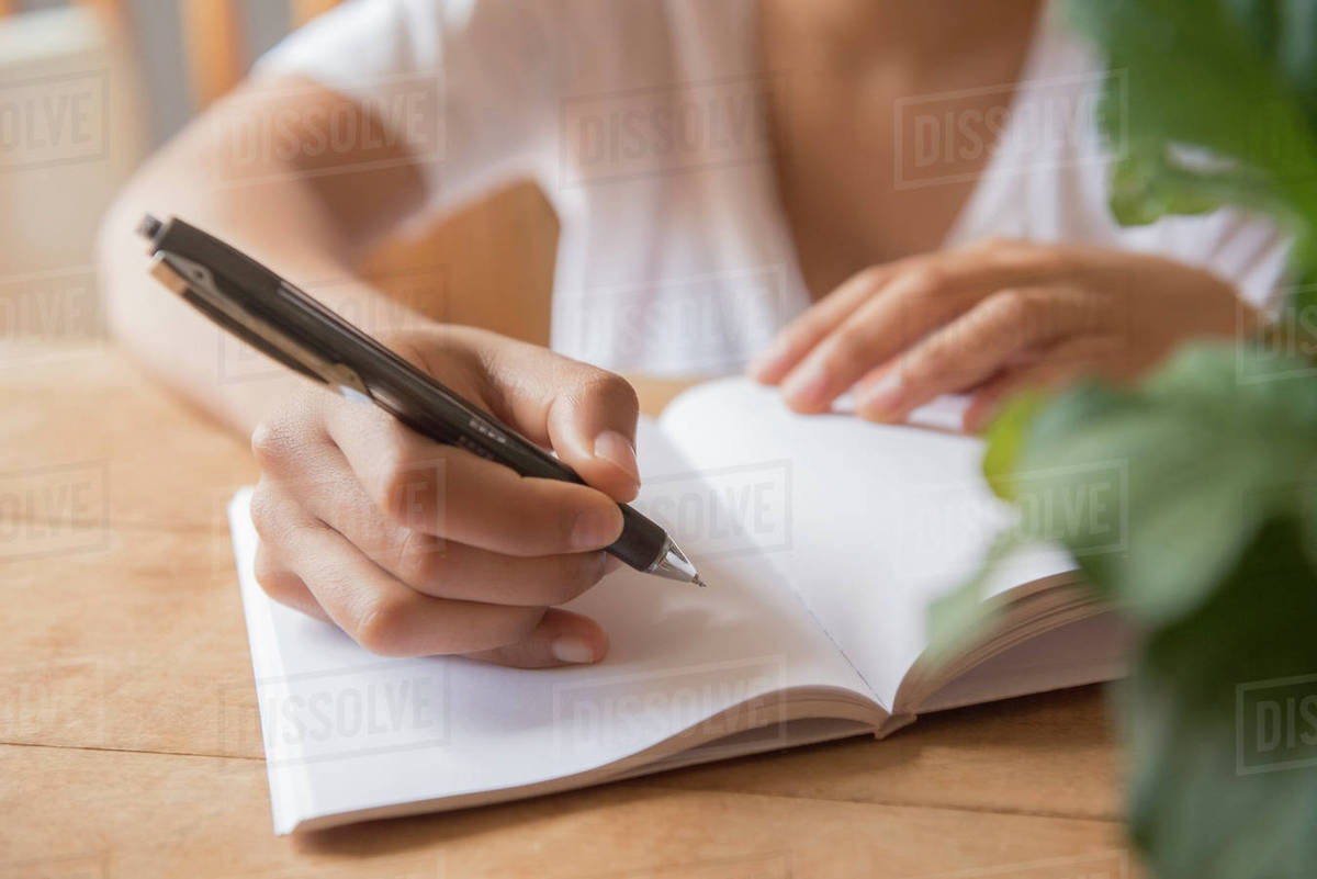 hands of african american woman writing in journal - stock photo