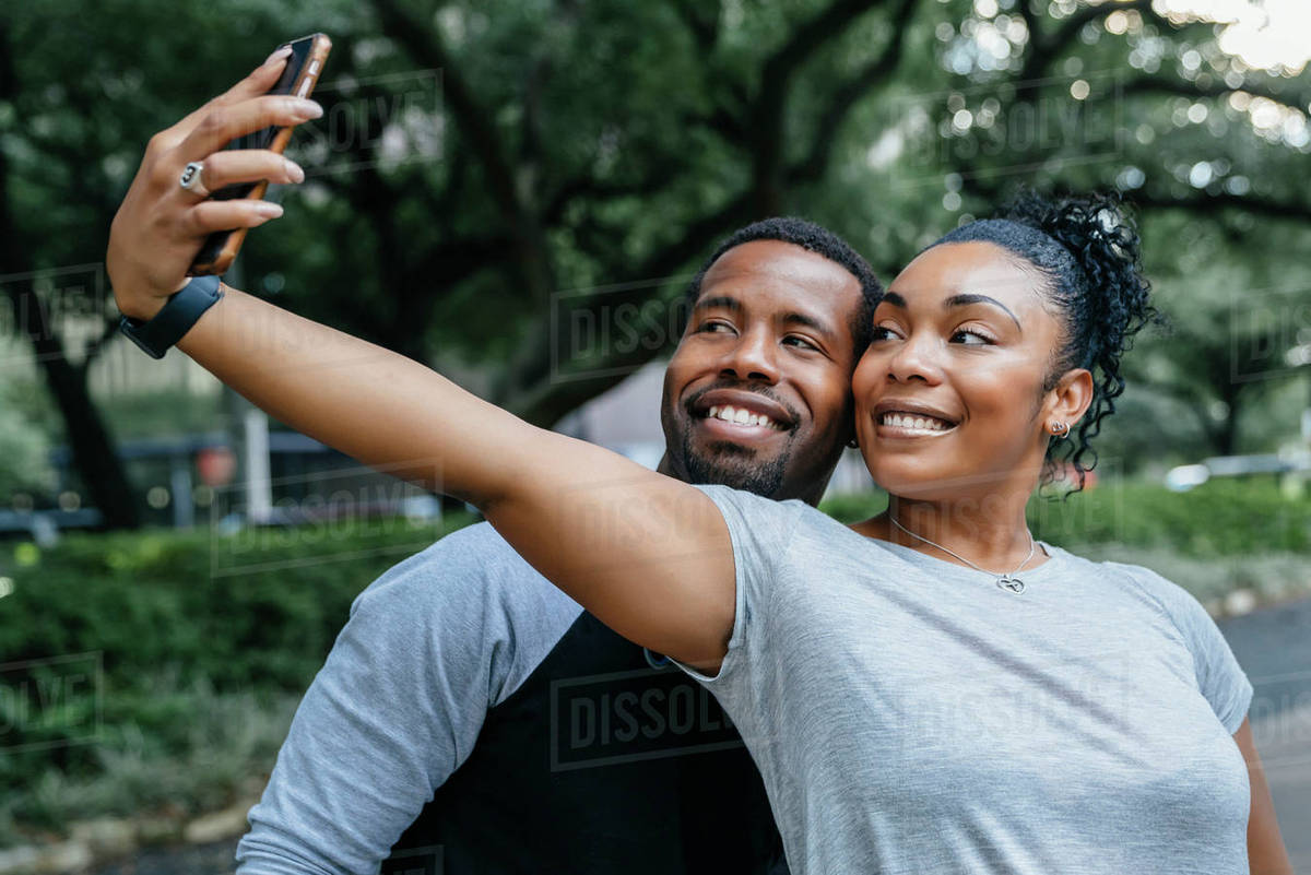 Smiling Black Couple Posing For Cell Phone Selfie