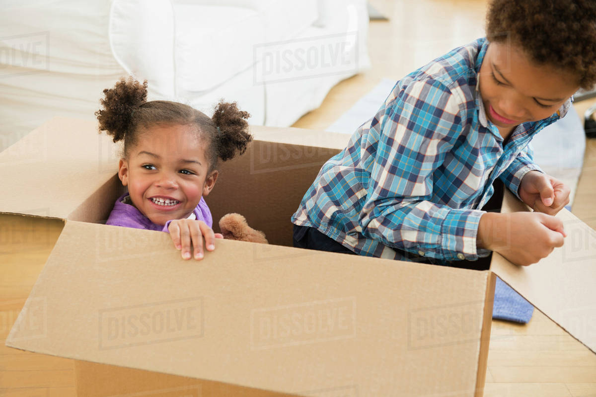 Black children playing in cardboard box - Stock Photo - Dissolve