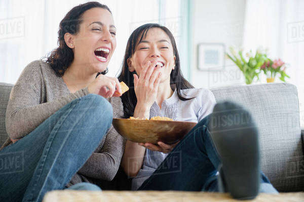 Women laughing on sofa together Royalty-free stock photo