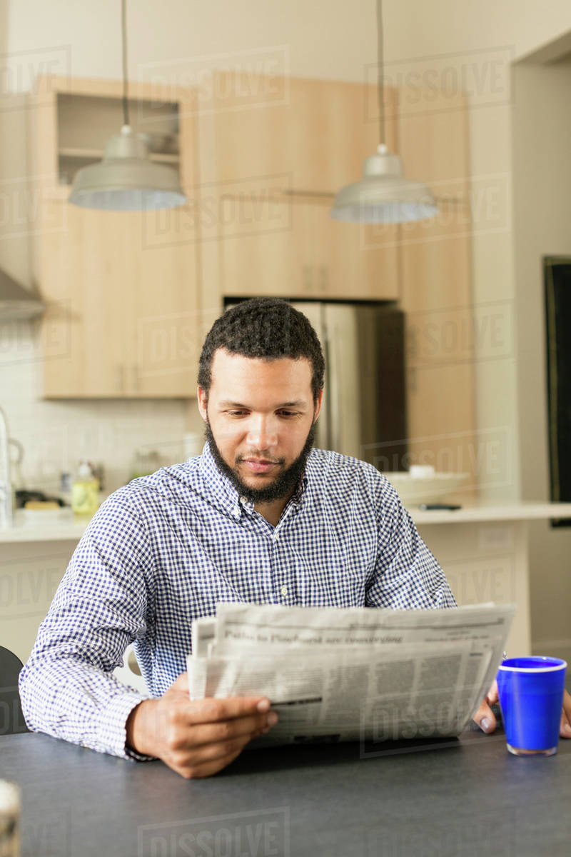 mixed race man reading newspaper at breakfast table - stock photo
