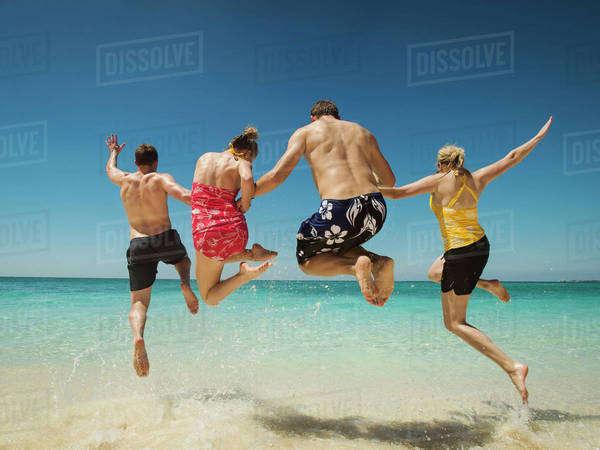 Caucasian couples jumping for joy in water on tropical beach Royalty-free stock photo