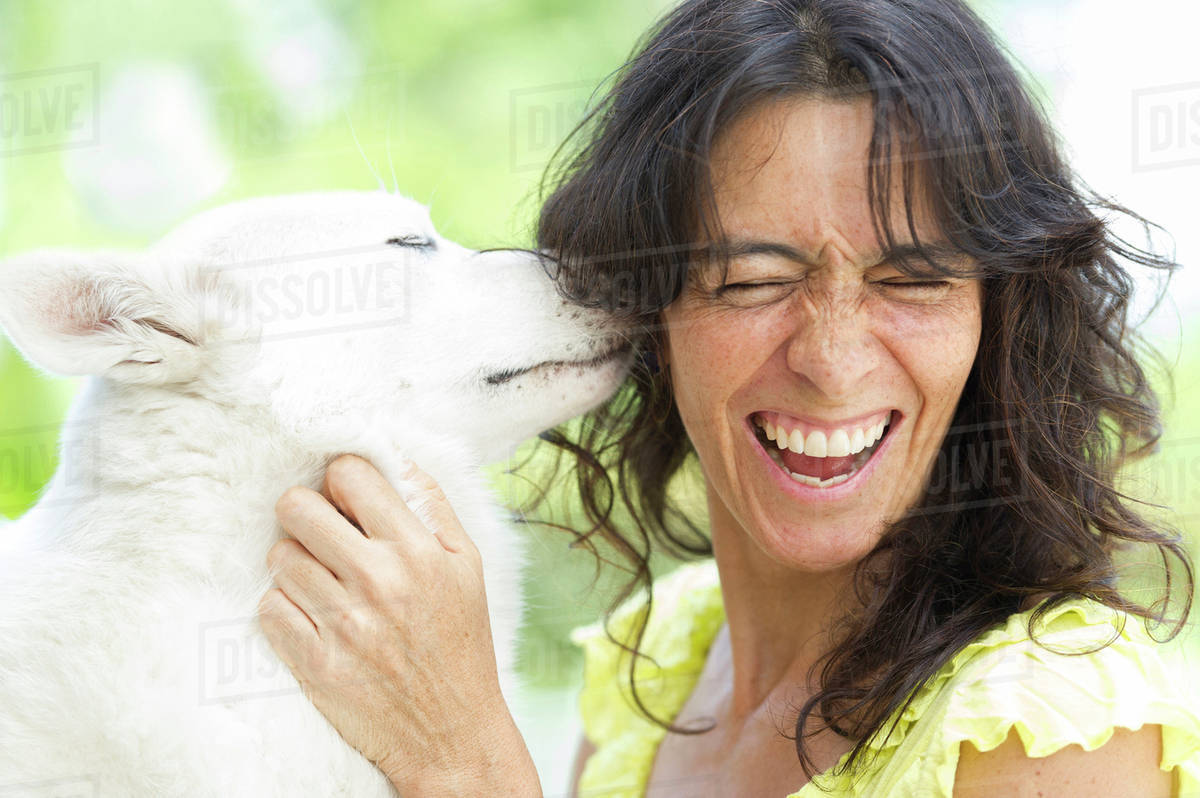 Hispanic woman playing with dog Royalty-free stock photo