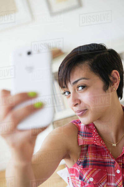 Mixed race woman taking selfie with cell phone Royalty-free stock photo