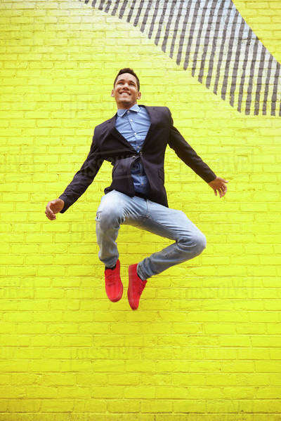 Smiling man jumping for joy near bright yellow wall Royalty-free stock photo