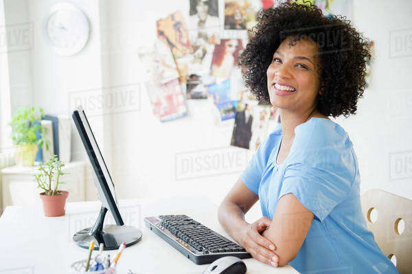Smiling woman using computer at desk Royalty-free stock photo