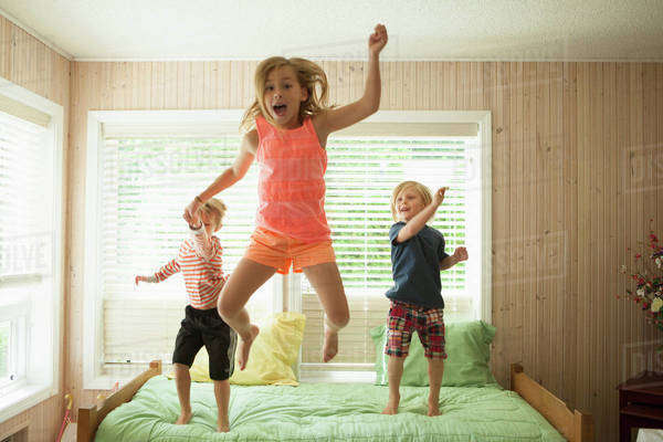 Caucasian children jumping on bed Royalty-free stock photo