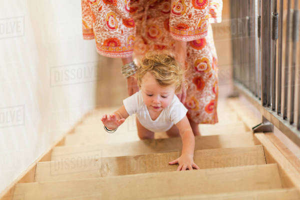 Caucasian mother helping baby son climb stairs Royalty-free stock photo