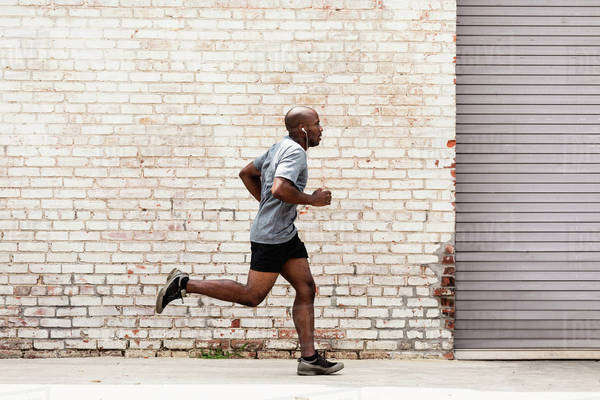 Black man running on city sidewalk Royalty-free stock photo
