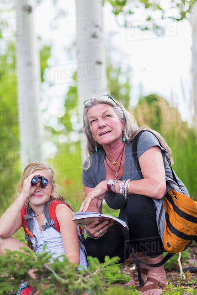Caucasian grandmother and granddaughter using binoculars while hiking Royalty-free stock photo