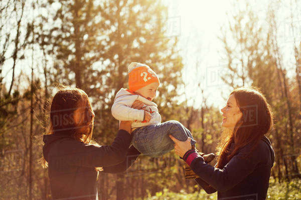 Women playing with baby boy outdoors Royalty-free stock photo