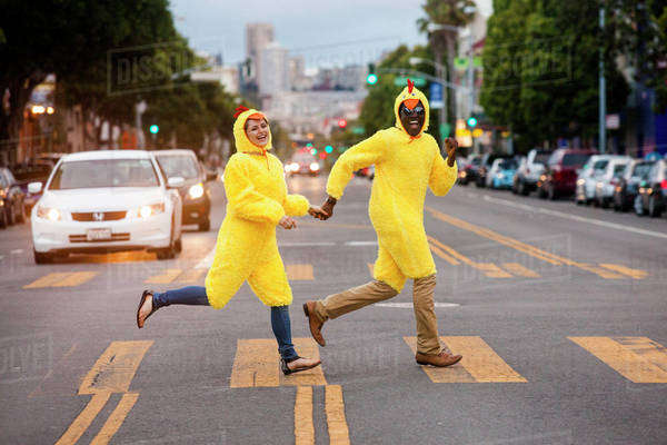 Couple in chicken costumes crossing city street Royalty-free stock photo