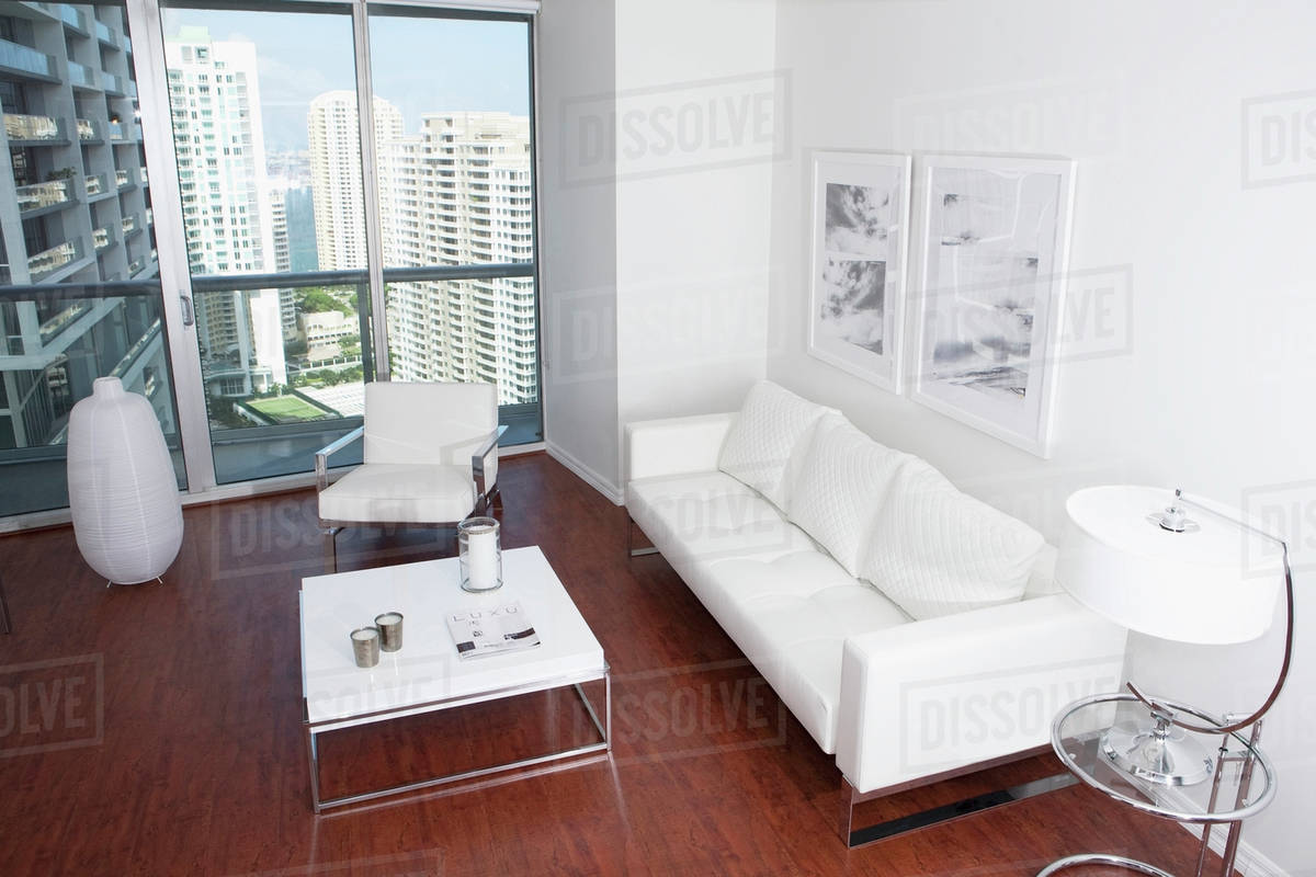 Sofa, coffee table and windows in modern apartment overlooking high ...