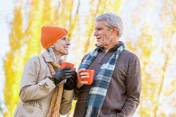 Older Caucasian couple drinking coffee near autumn trees Royalty-free stock photo