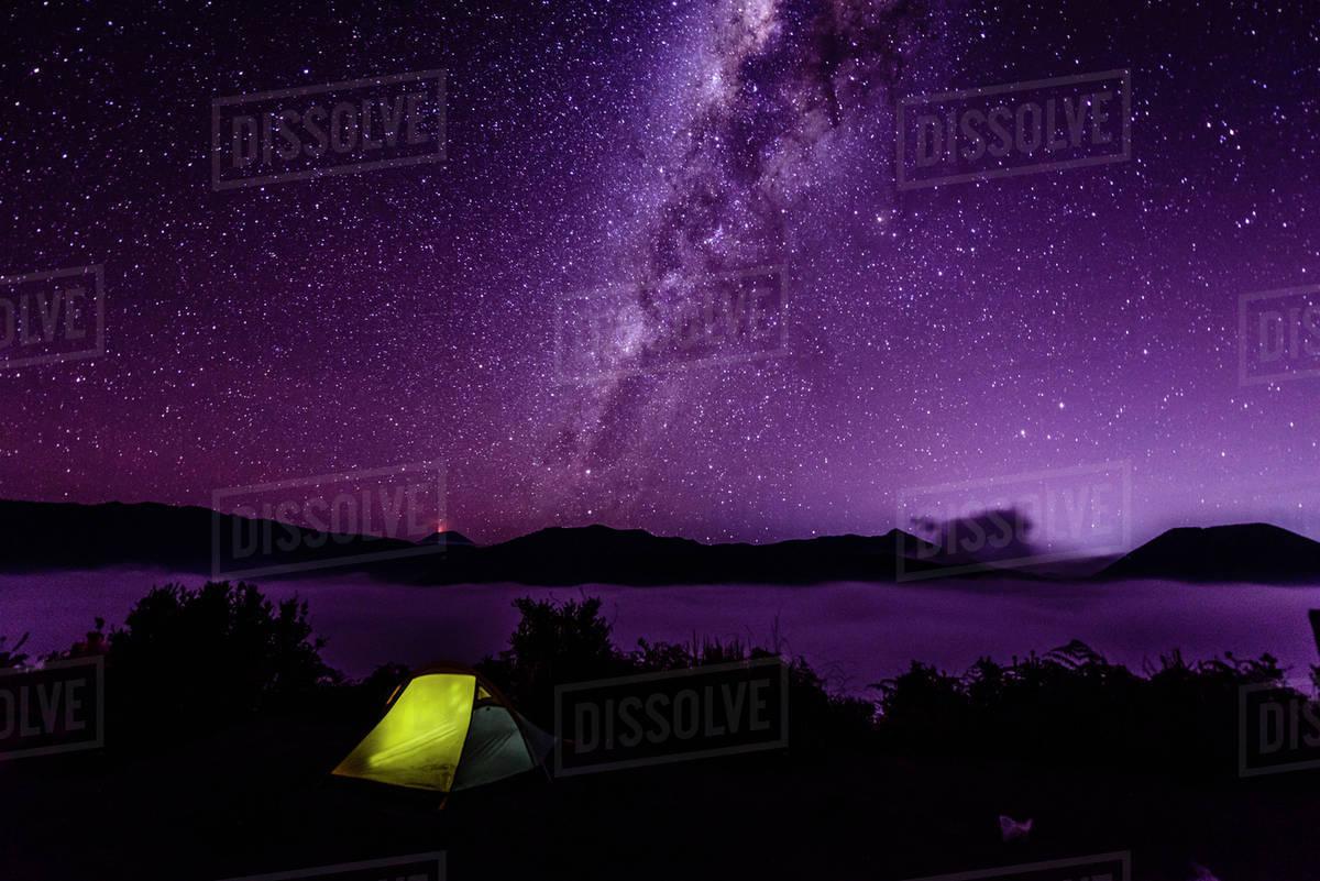 Milky Way galaxy over campsite in starry night sky stock photo