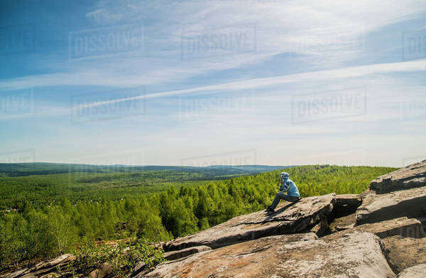 Caucasian climber sitting on rock formation Royalty-free stock photo